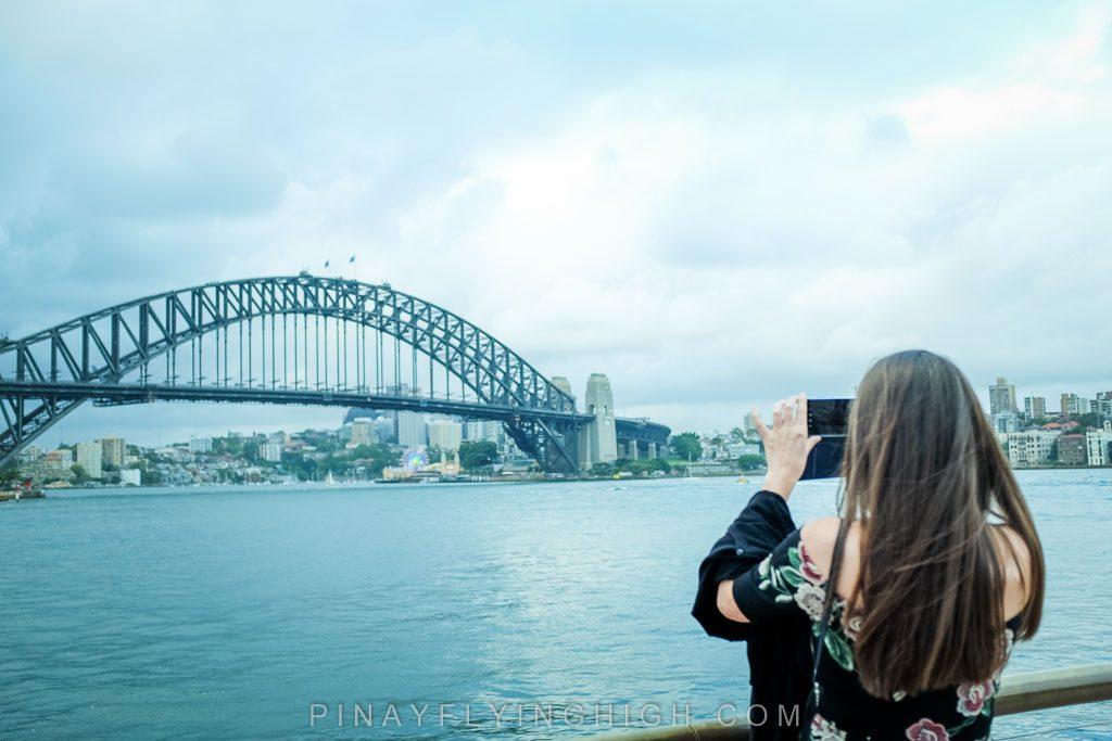 Girl taking a photo of Sydney Harbour Bridge