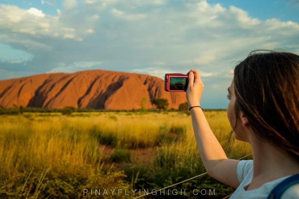 Girl taking photo of Uluru Rock.