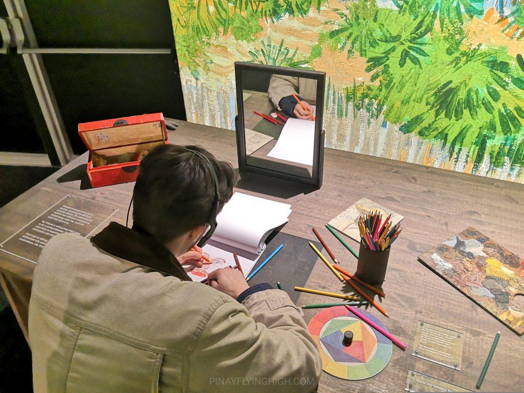 an artist drawing a self-portrait at meet vincent van gogh experience